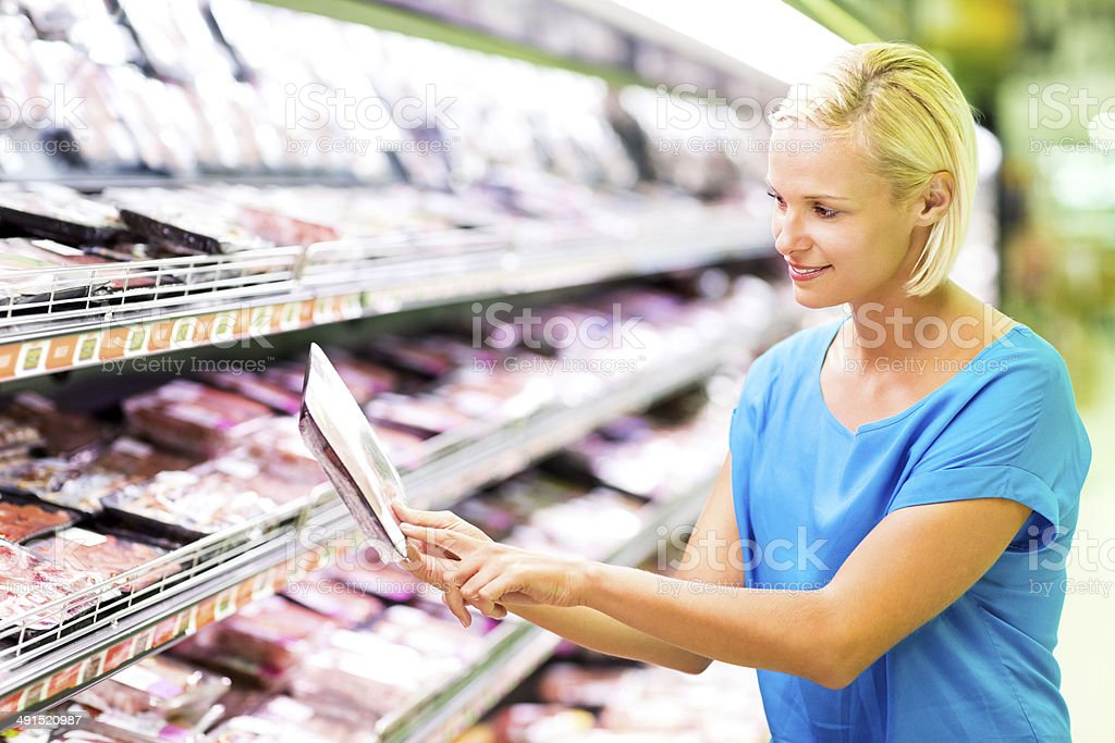 Woman Checking Product Label While Shopping In Grocery Store royalty-free stock photo