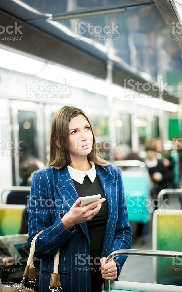 Woman Checking Public Transport Directions Before Getting Off Train stock photo