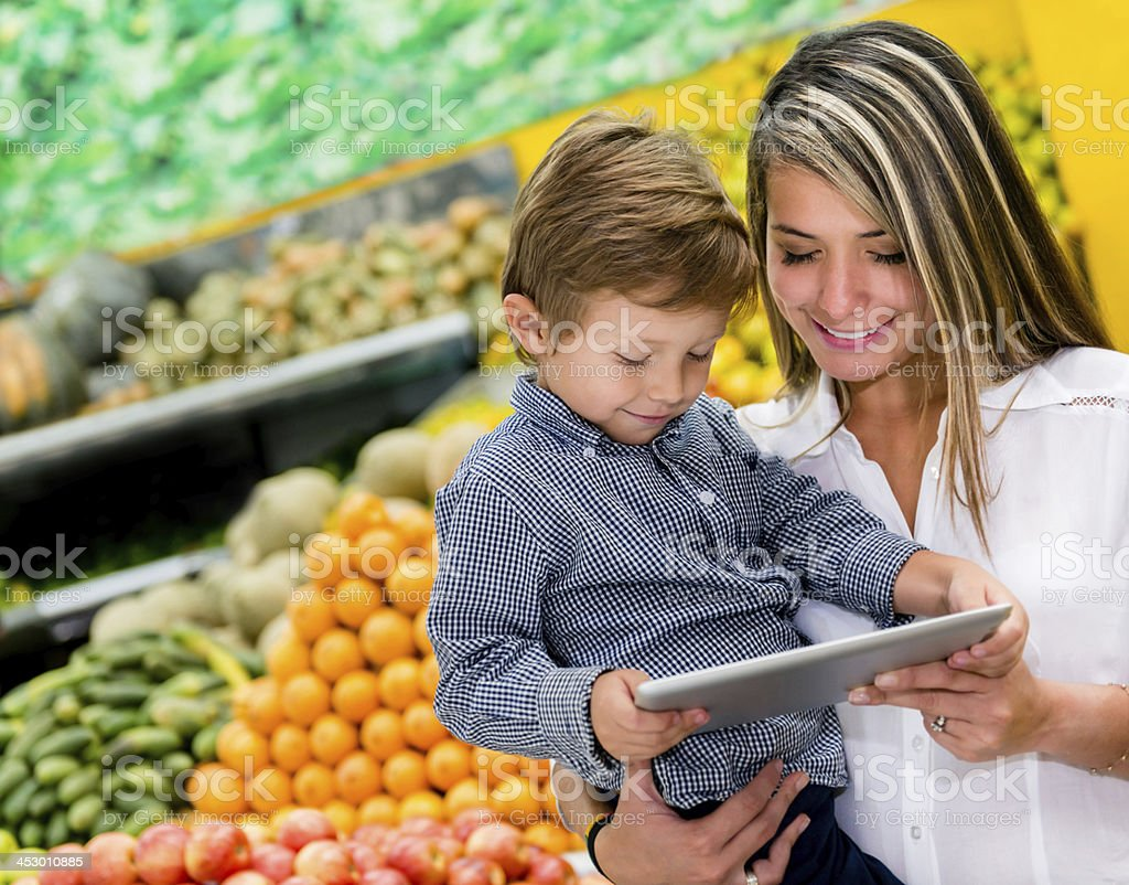 Woman checking shopping list on a digital tablet royalty-free stock photo