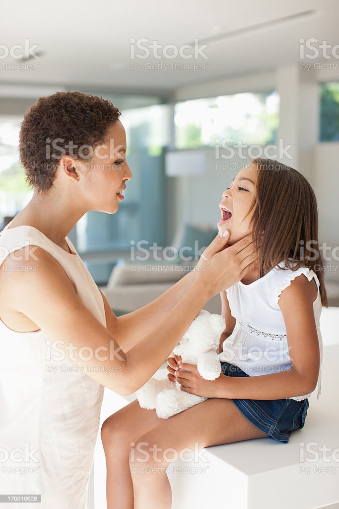 Woman checking sick daughter's throat royalty-free stock photo