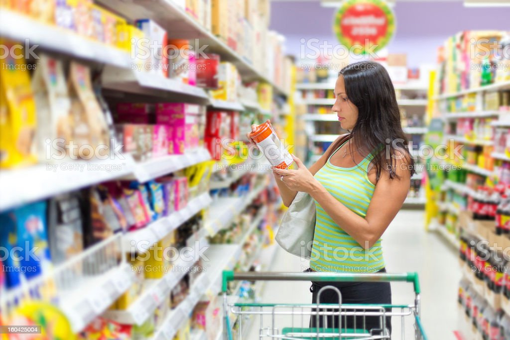 Woman checking the food labels in the supermarket stock photo