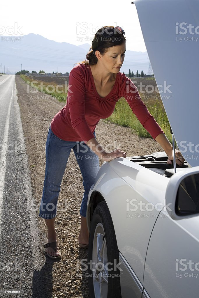 Woman checking under hood of car royalty-free stock photo