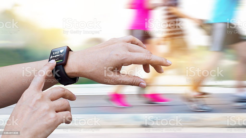 Woman checking up heart rate from smart watch stock photo