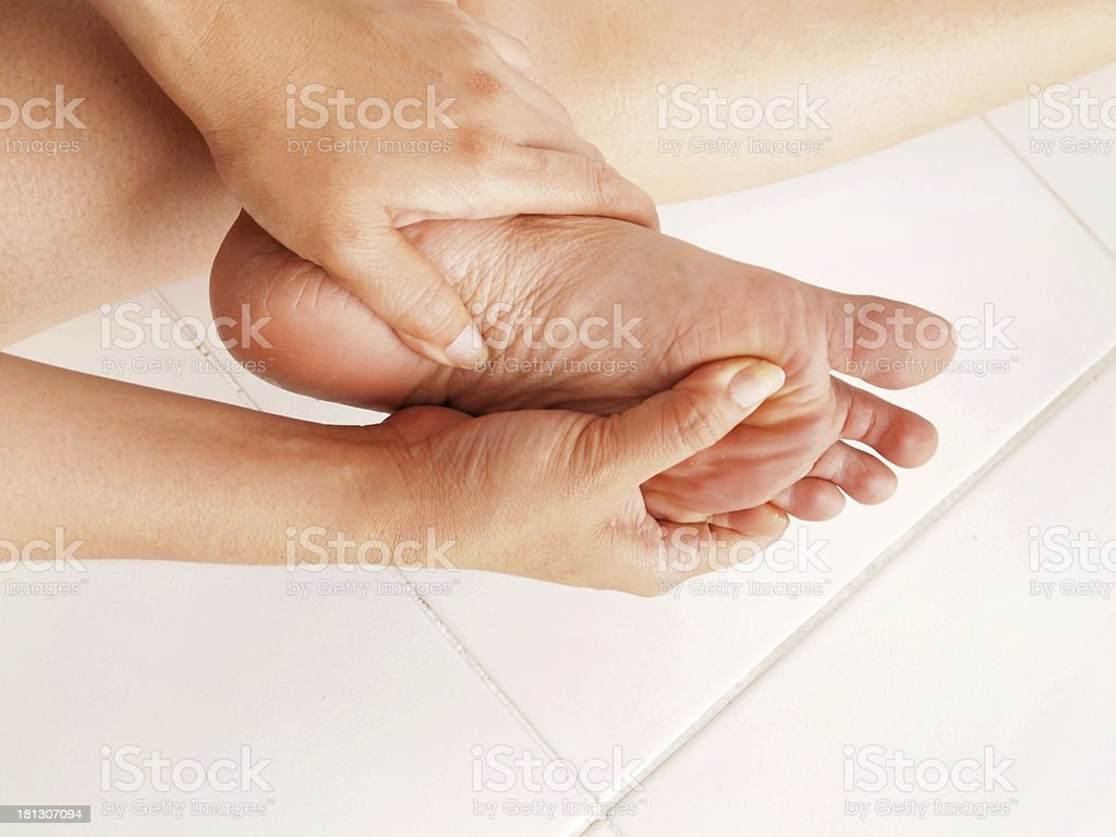 woman checks her aching foot royalty-free stock photo