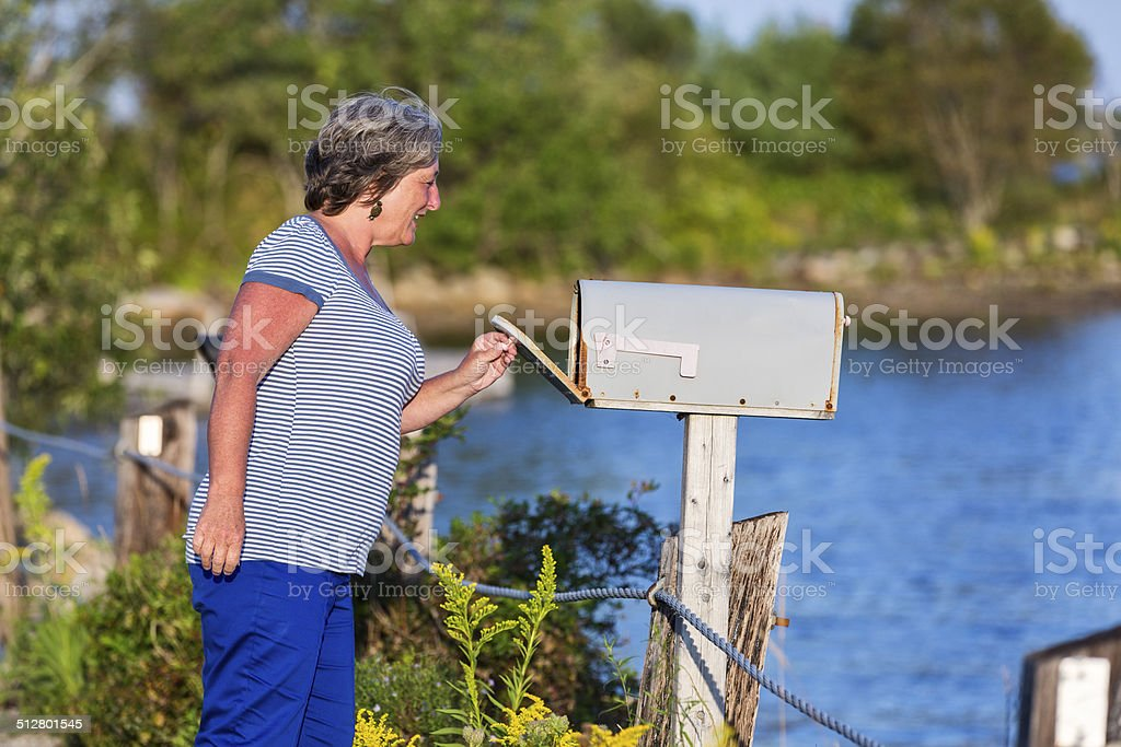 Woman Checks Her Mailbox for Mail stock photo