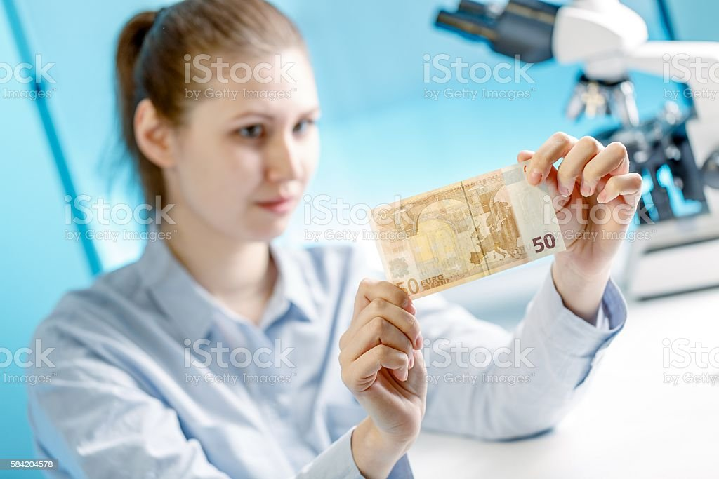 Woman checks the authenticity of Euro banknotes stock photo