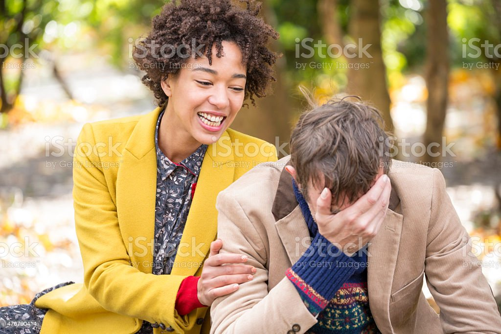 Woman cheering a depressed man in park. stock photo