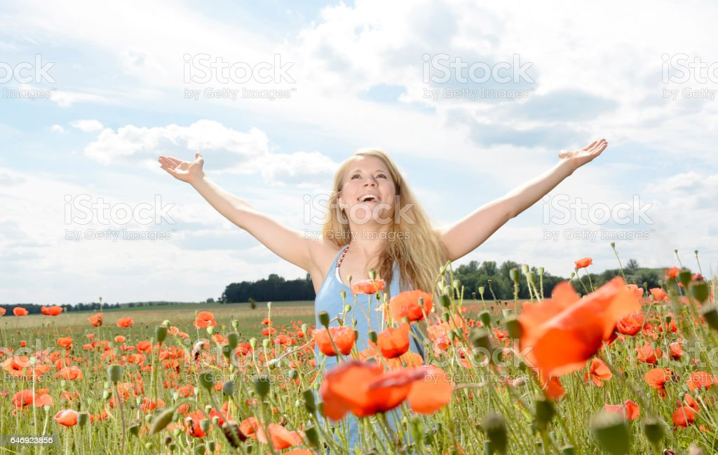 woman cheering in poppy field stock photo