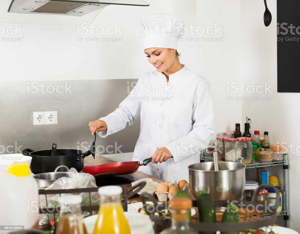 Woman chef cooking food at kitchen stock photo