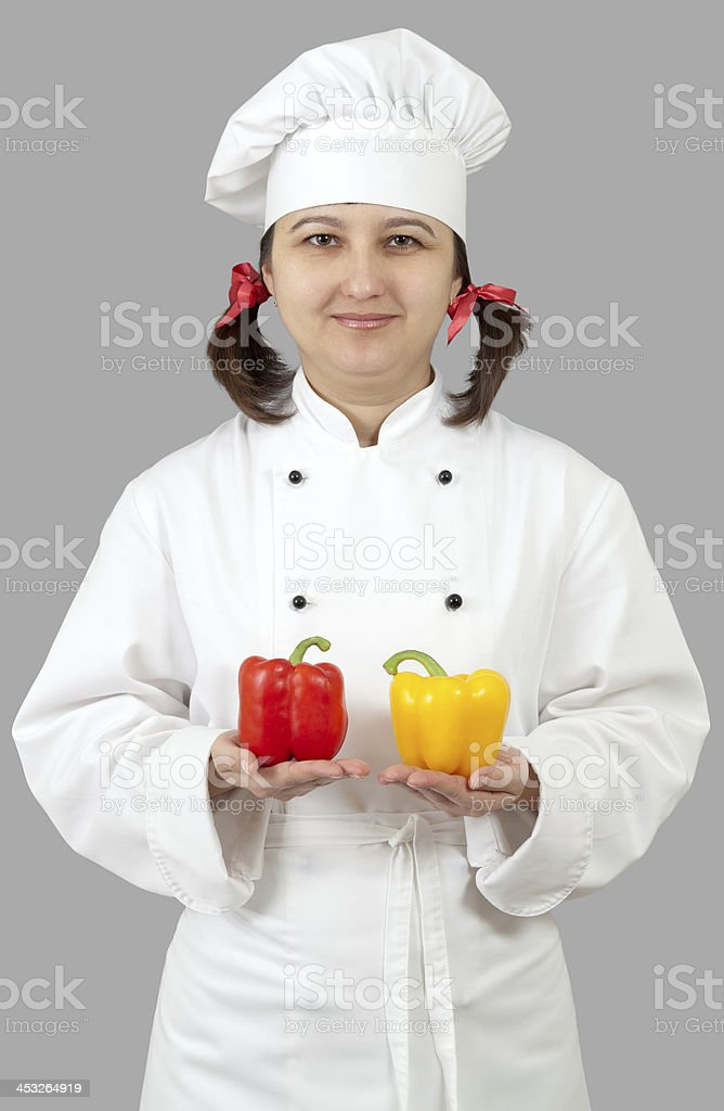 Woman chef holding a yellow and red peppers. royalty-free stock photo