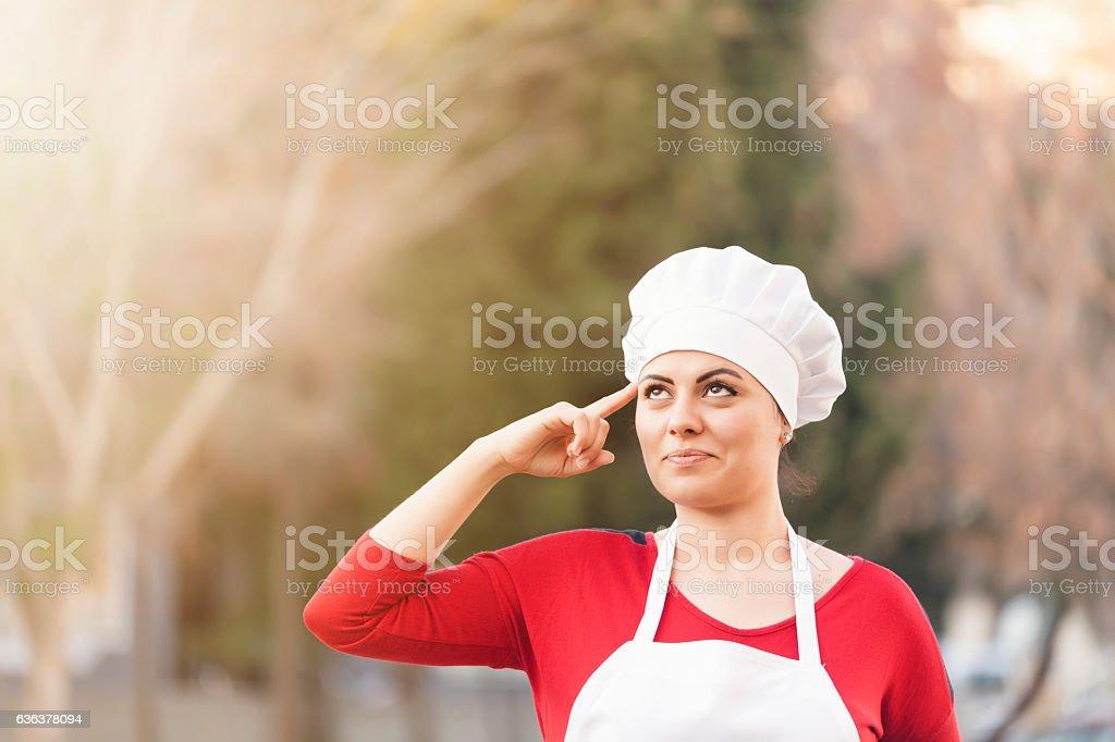 Woman Chef thinking bokeh background stock photo