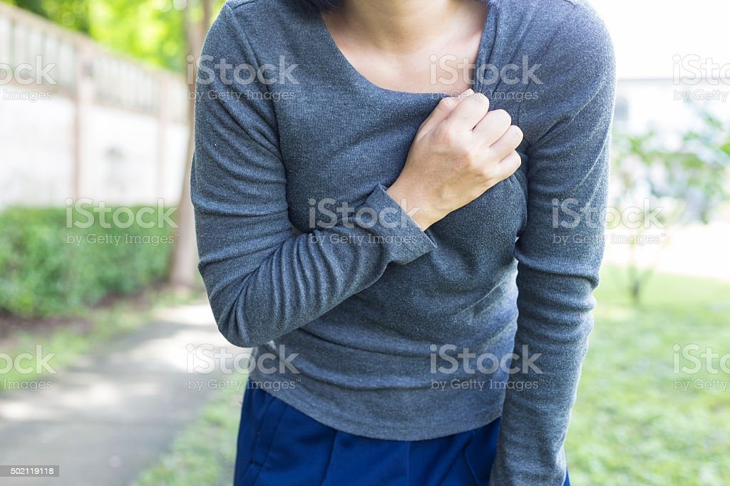 Woman: Chest pain at Park stock photo
