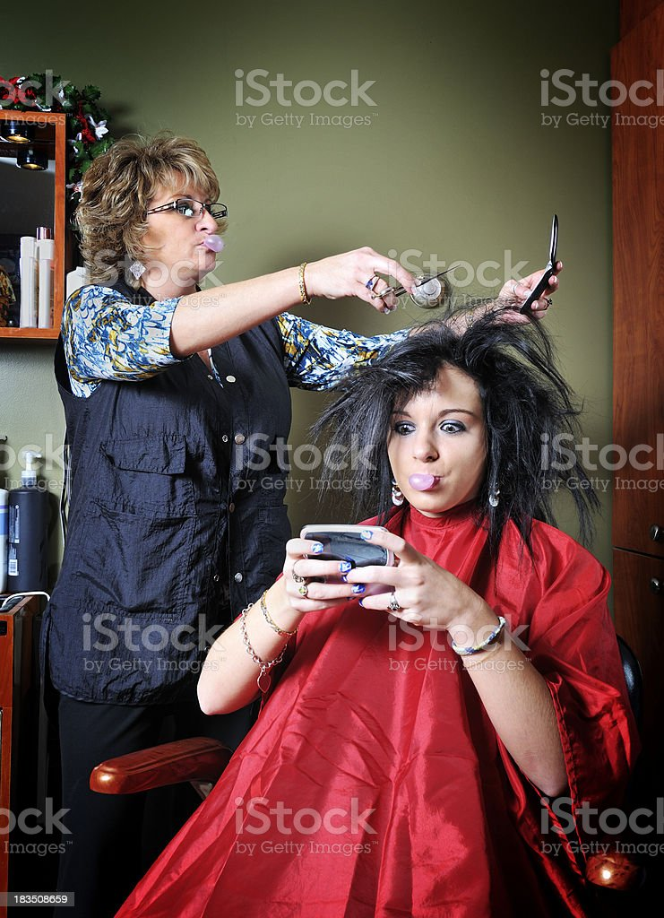 Woman chewing gum using cell phone while getting hair done. royalty-free stock photo