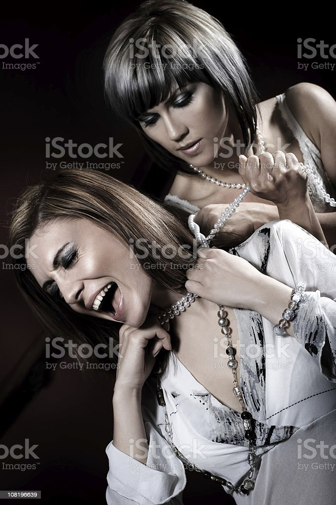 Woman Choking Female with Necklace stock photo