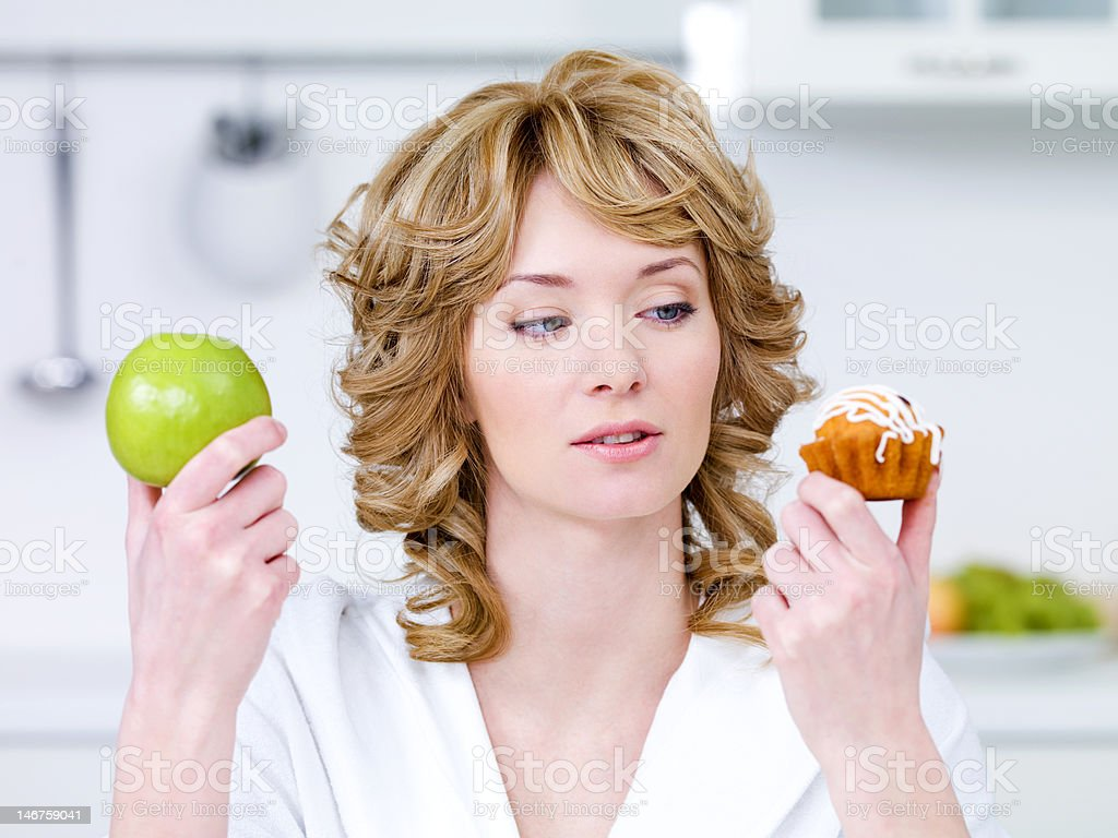 Woman choose between cake and apple stock photo