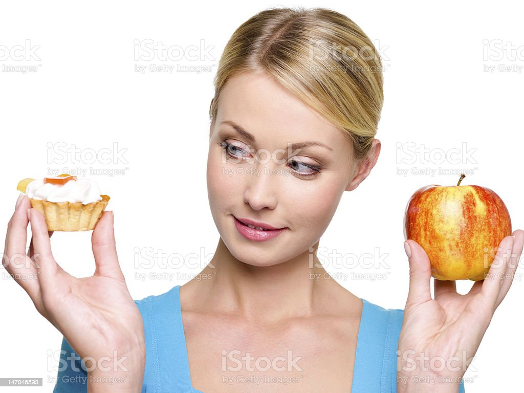 woman choose  from sweet cake and red apple stock photo