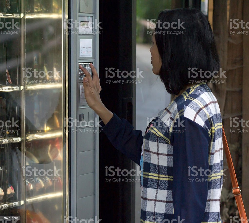 Woman chooses goods from vending machine stock photo
