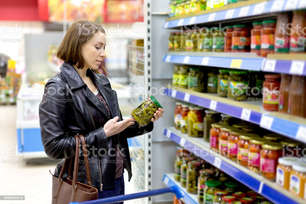 woman chooses pickle stock photo