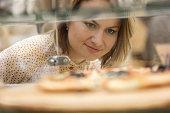 Woman chooses pizza at bakery