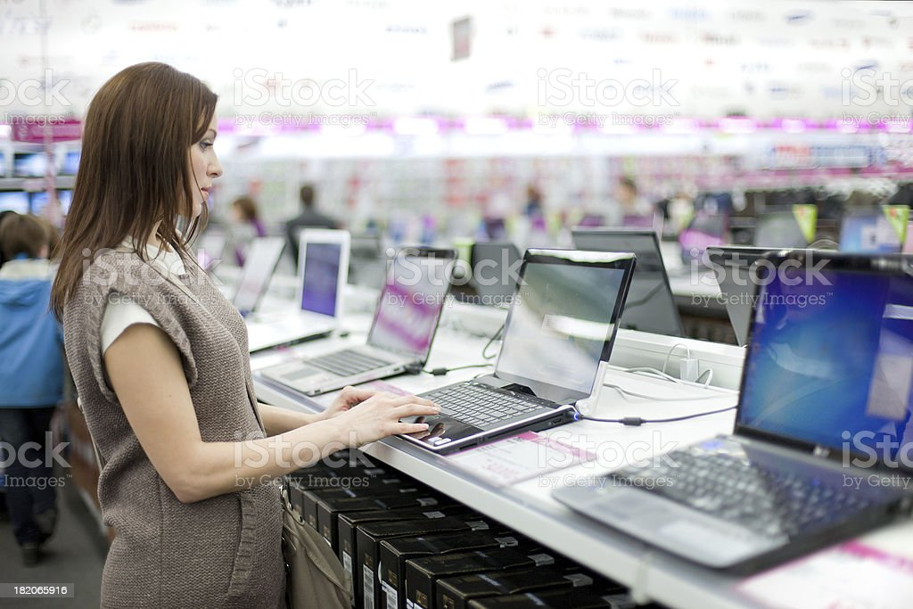 woman chooses the laptop stock photo