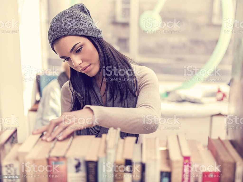 Woman choosing a book in library. stock photo