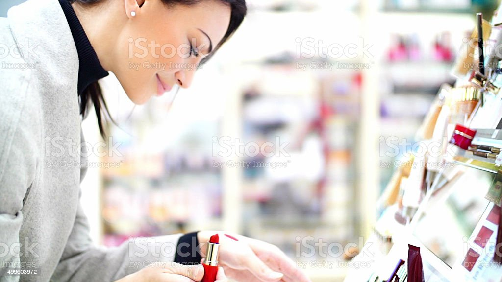 Woman choosing a lipstick at beauty store. stock photo