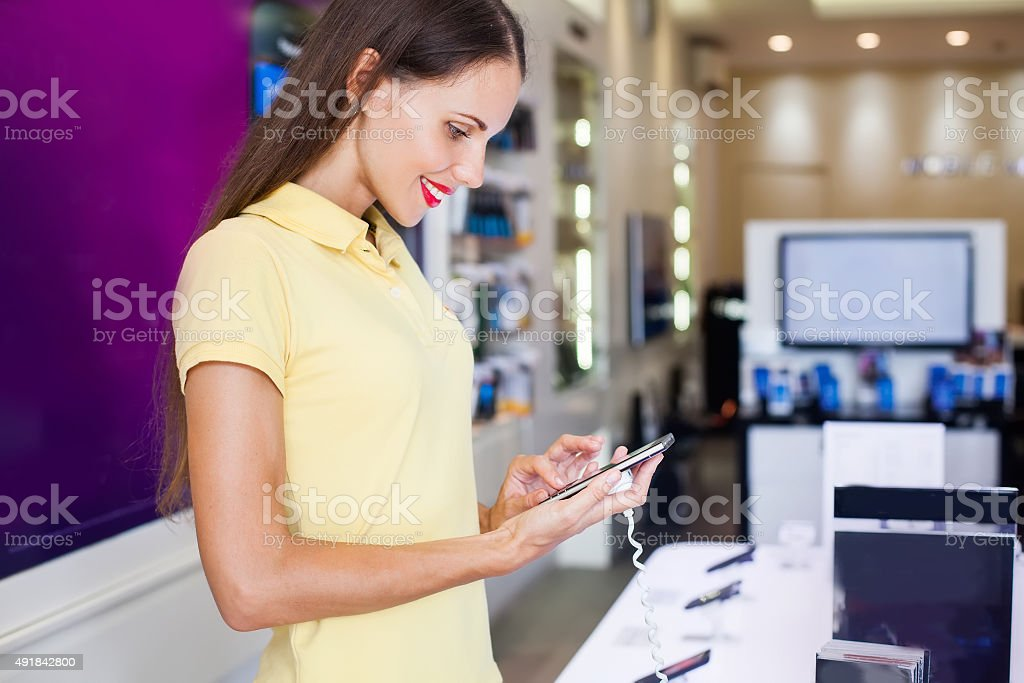 woman choosing a new mobile phone in a shop stock photo