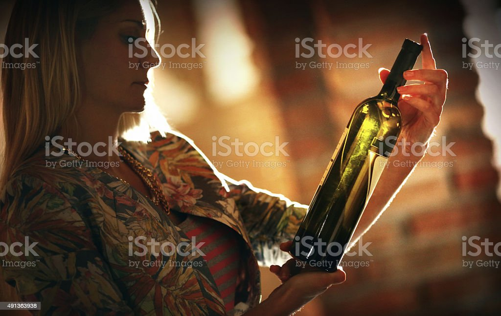 Woman choosing a wine in wine cellar. stock photo