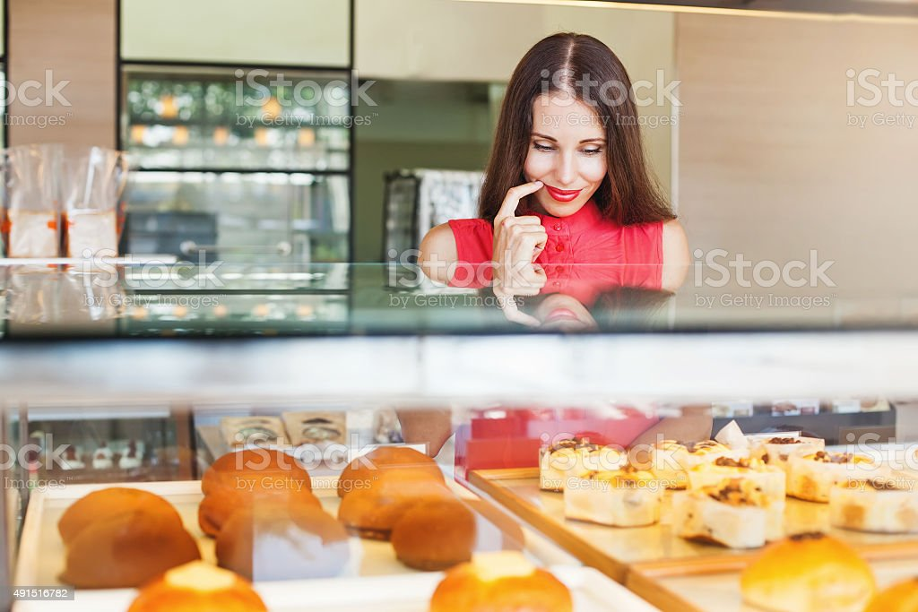 woman choosing bakery items in a shop stock photo