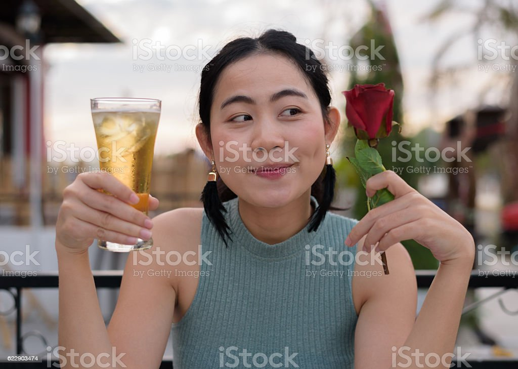 Woman choosing beer or rose in a restaurant stock photo
