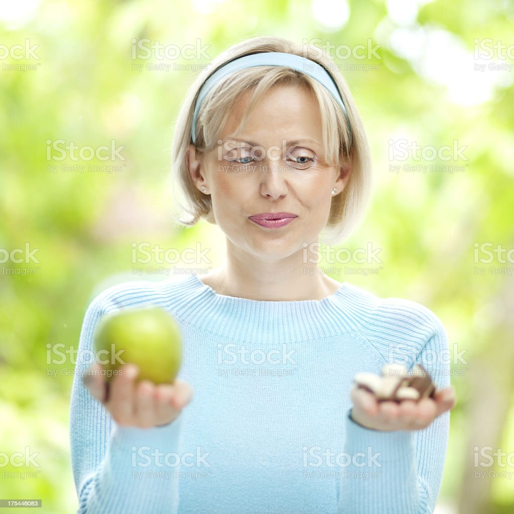 Woman choosing between apple and chocolate royalty-free stock photo