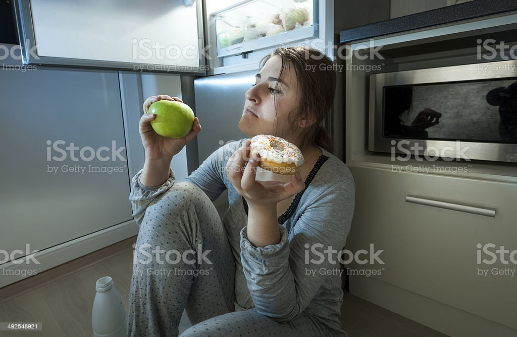 woman choosing between apple and donut at evening lunch stock photo