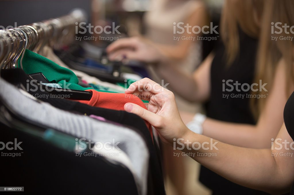 Woman choosing clothes on rack, closeup stock photo