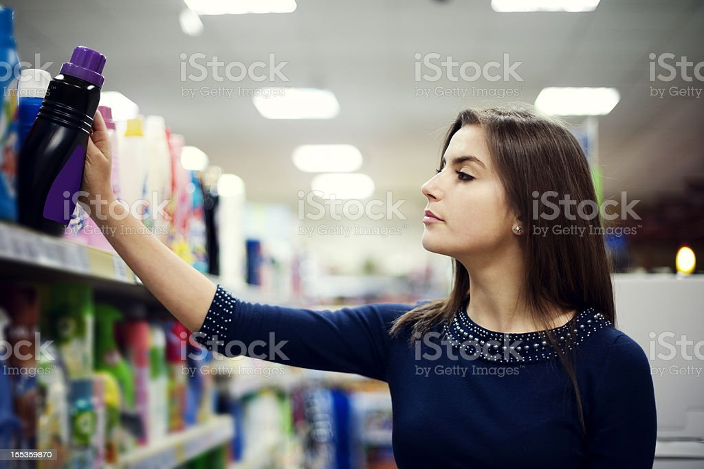 Woman choosing detergent in supermarket stock photo
