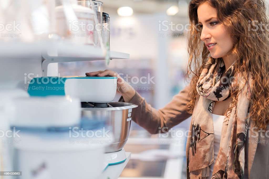 Woman choosing electric mixer stock photo