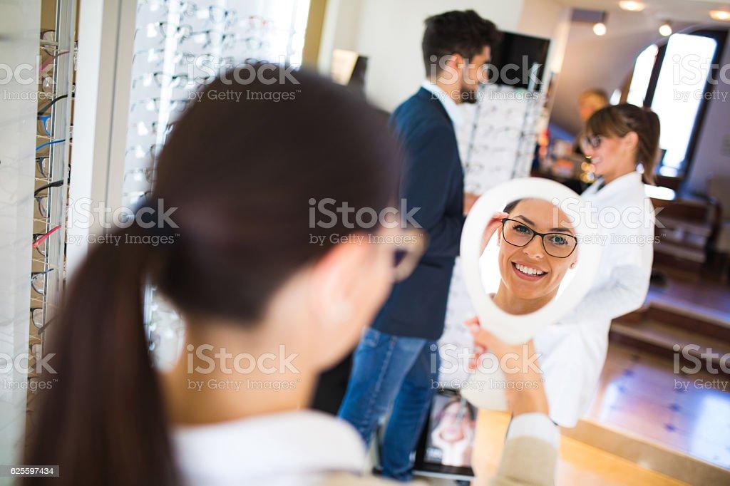Woman choosing eyeglasses in optical store using mirror stock photo