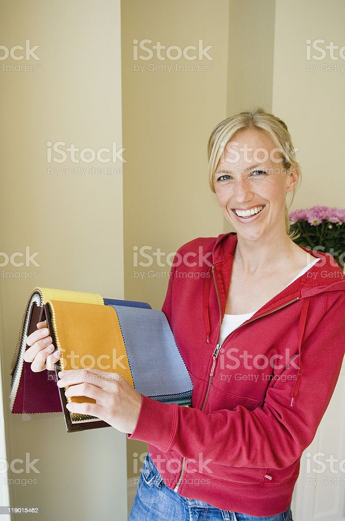 Woman choosing fabric in new home stock photo