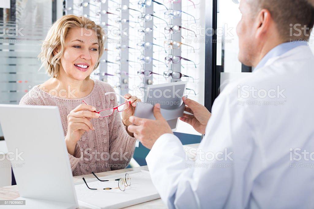 Woman choosing glasses in optics store stock photo