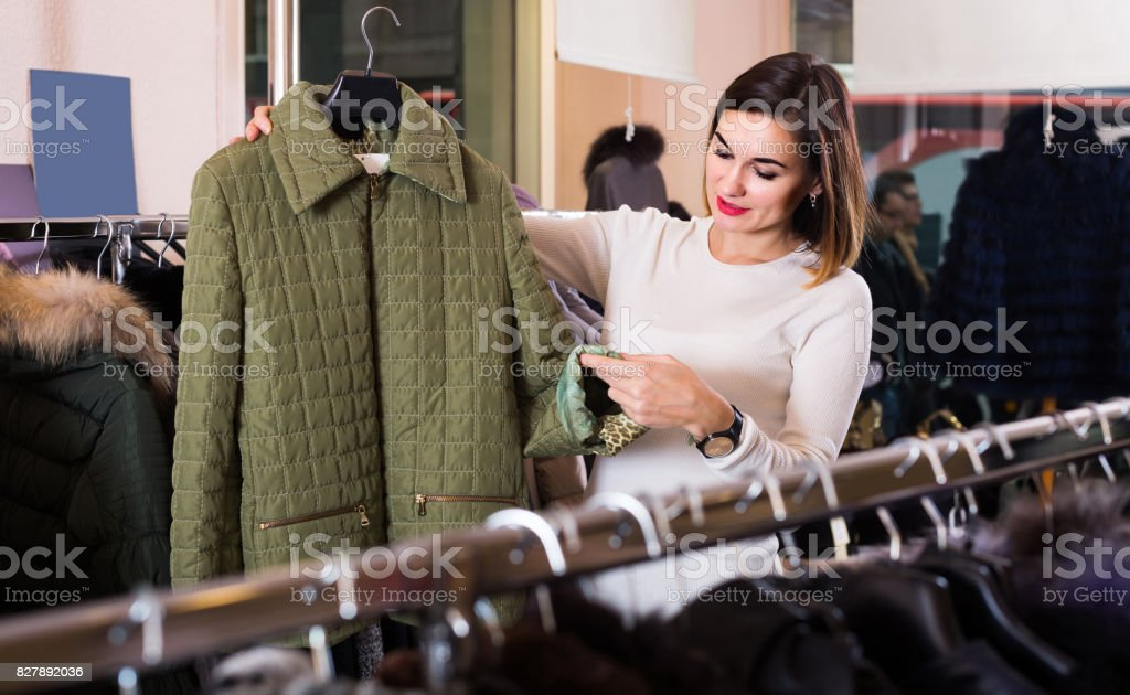 woman choosing green quilted jacket in women's cloths store stock photo