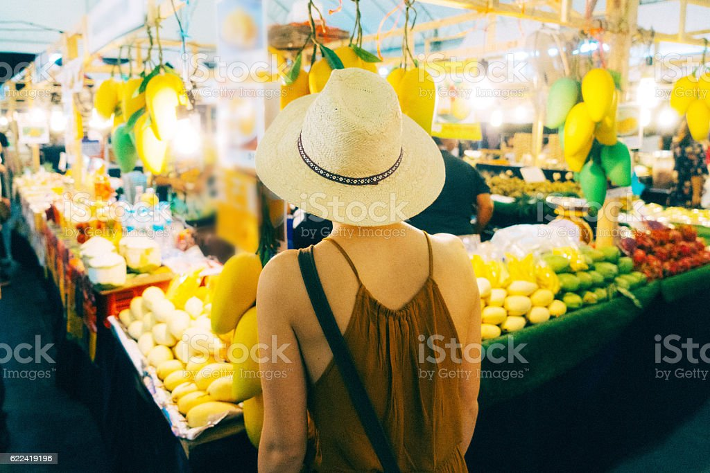 Woman choosing mango in market stock photo