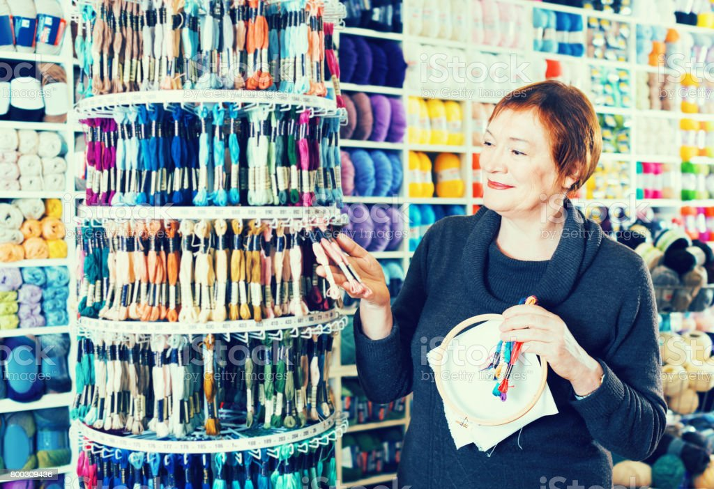 Woman choosing mouline for embroidery in needlework shop stock photo