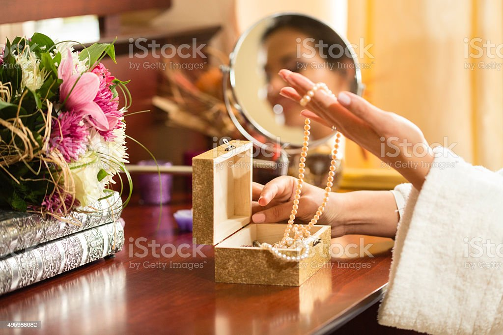 Woman choosing necklace from jewelry box stock photo