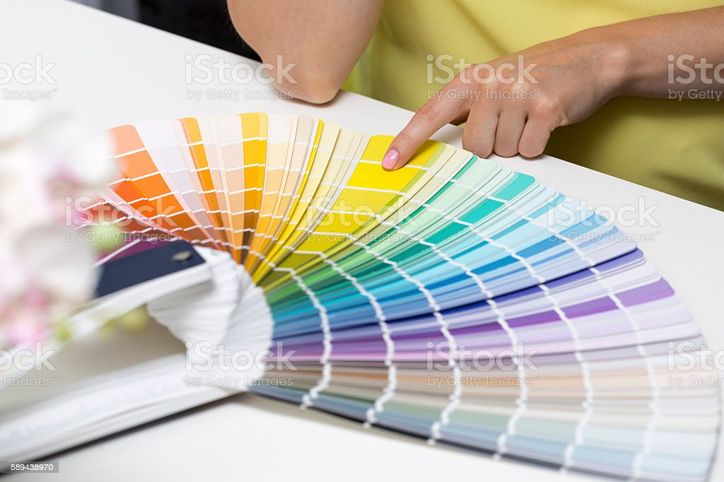 woman choosing paint color from tone samples stock photo