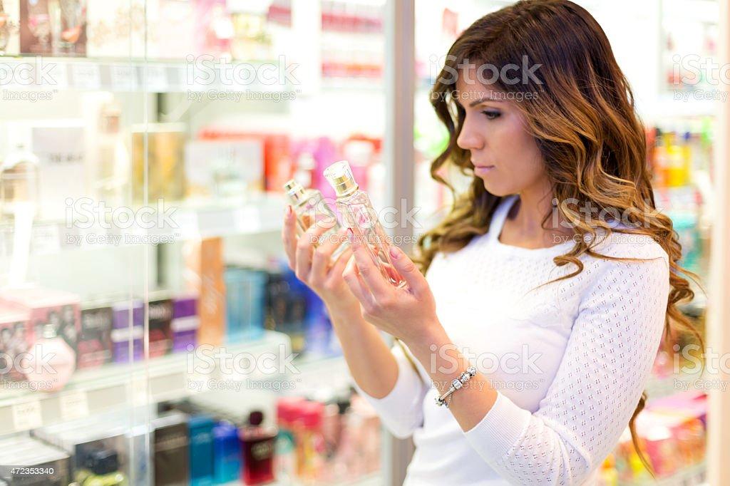 Woman choosing parfume in shopping mall stock photo