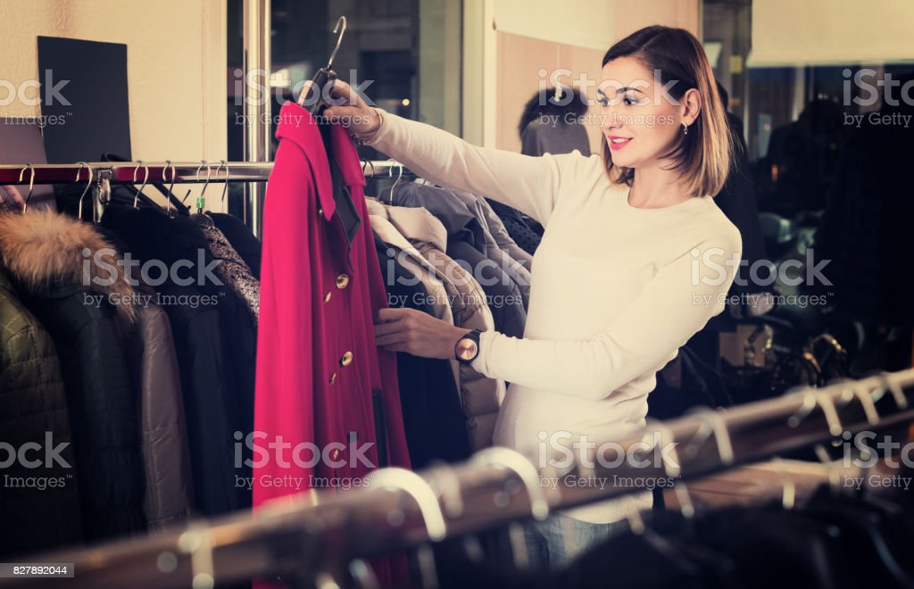 woman choosing red woolen coat in women's cloths store stock photo