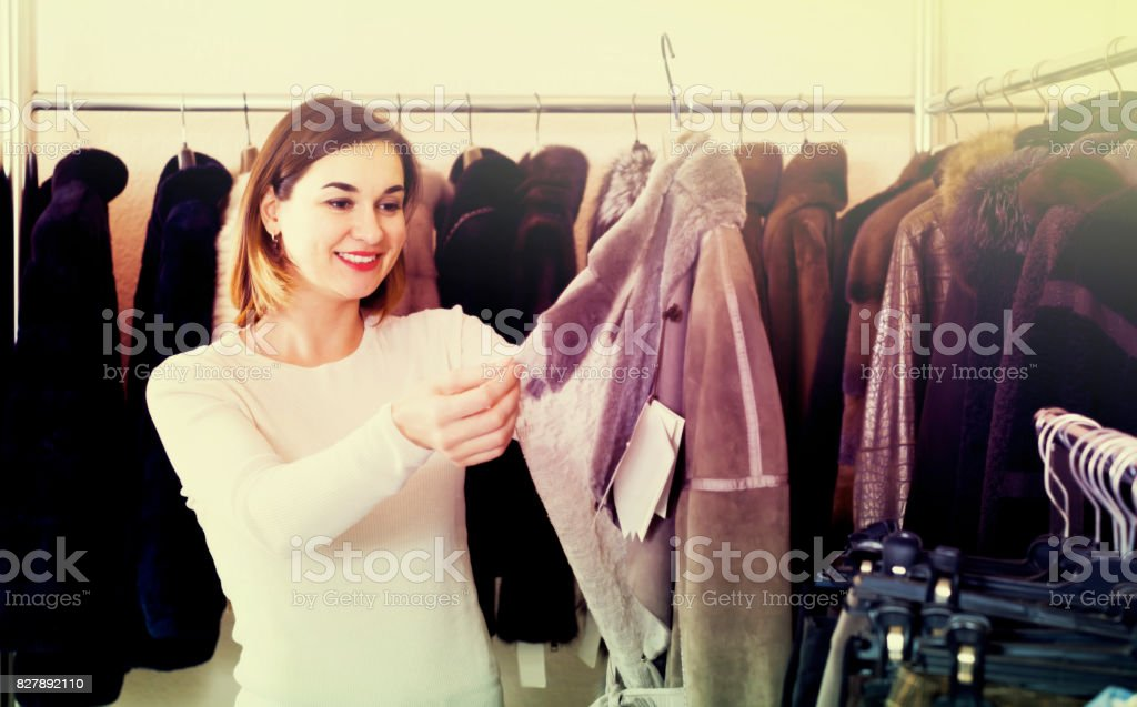 woman choosing sheepskin coat in women's cloths store stock photo