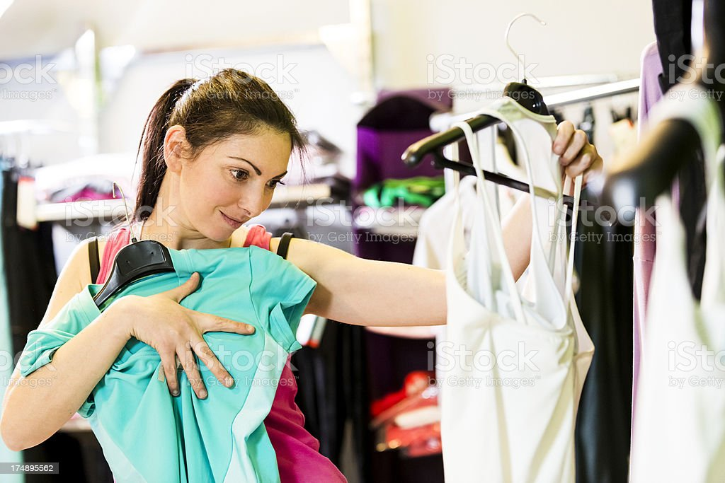 Woman choosing sports clothes to buy in store royalty-free stock photo