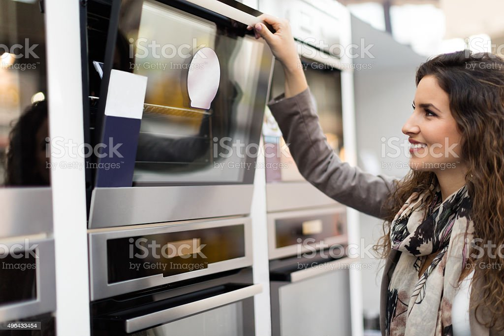 Woman choosing stove stock photo