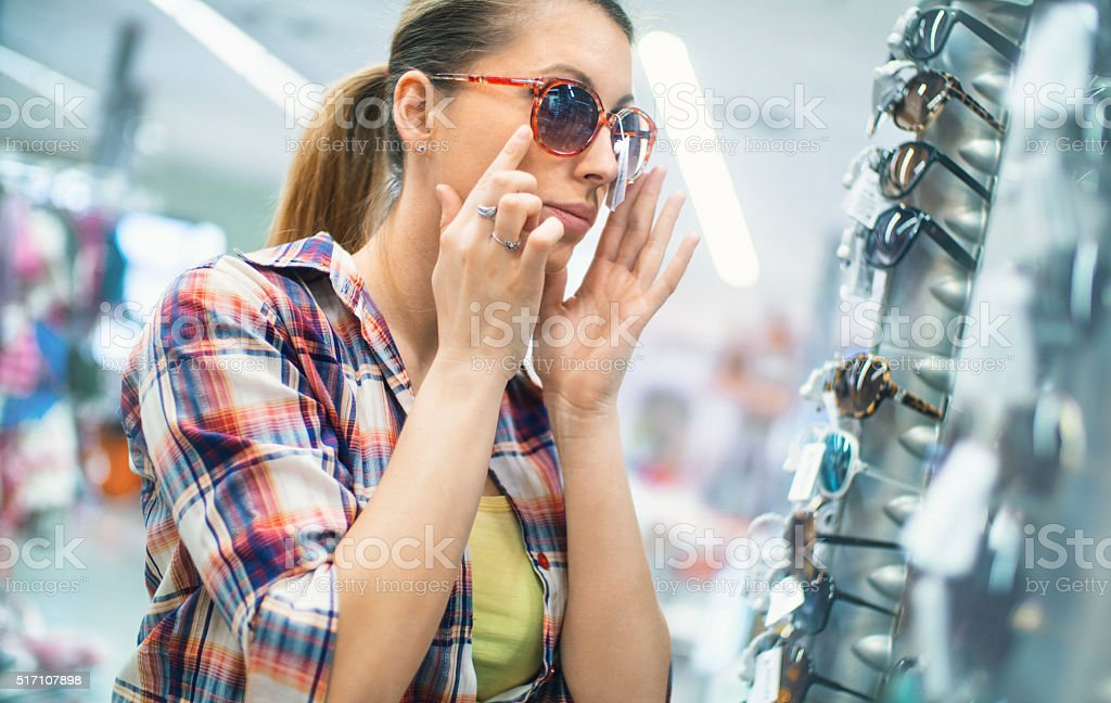Woman choosing sunglasses at a retailer. stock photo