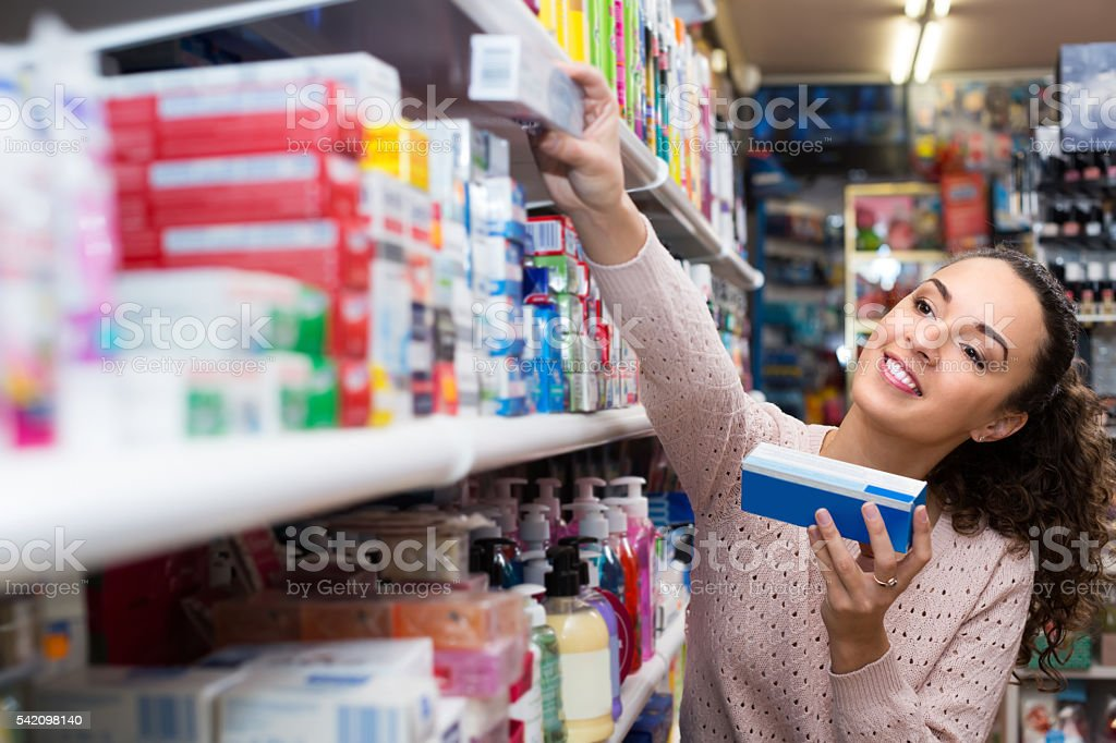 Woman choosing toothpaste in supermarket stock photo